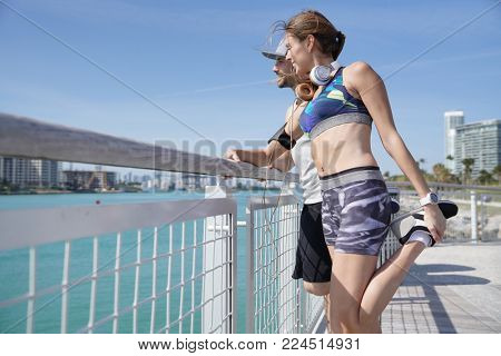 Joggers stretching out after running on Miami waterfront pier