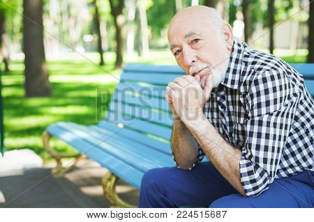 Thoughtful senior man outdoors. Elderly man in casual sitting on the bench in sunny park, looking on camera, copy space