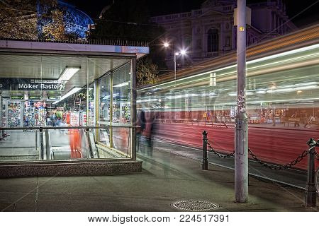 VIENNA, AUSTRIA - SEPTEMBER 12, 2013: Long night exposure outside public station Molker Bastei. A station store with incidental people and a red tram passing by, Vienna September 12, 2013.