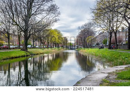 DUBLIN, IRELAND - APRIL 21, 2016: Perspective view of a city river with buildings on both sides in Dublin April 21, 2016. Incidental people passing by and resting on benches.