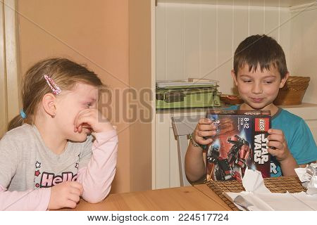 HUSTOPECE, THE CZECH REPUBLIC - JANUARY 13, 2018: Boy celebrating the ninth birthday. The birthday present is LEGO Star Wars. Brother and his disappointed sister.
