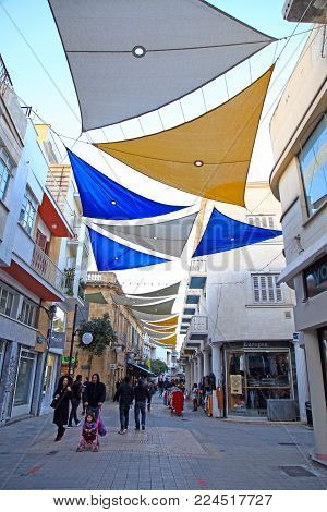 NICOSIA, CYPRUS - JANUARY 13, 2018: Tourists walking in Ledra street with cafes, bars, souvenir shops and boutiques in Nicosia, Cyprus. Ledra street connecting the 2 sides of Nicosia (Lefkosia), the last divided capital of the world.
