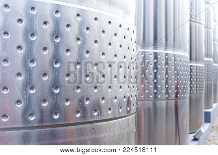 Modern technological industrial equipment of wine factory..Big stainless steel wine distilling tanks close up.