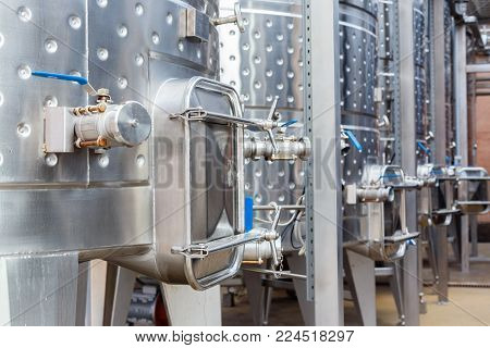 Modern technological industrial equipment of wine factory. Big stainless steel wine distilling vats.