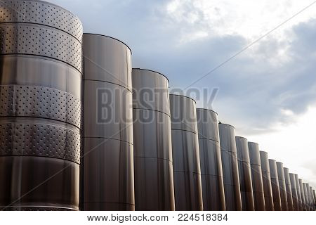 Modern technological industrial equipment of wine factory..Large stainless steel wine distilling vats on sky background.