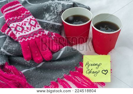 Kyiv UA, 21-12-2017, 2018 Winter Olympic Games in PyeongChang, Republic of Korea, Snow-covered scarf and gloves on snow, two cups of fans with coffee and a sticker - PyeongChang with love.