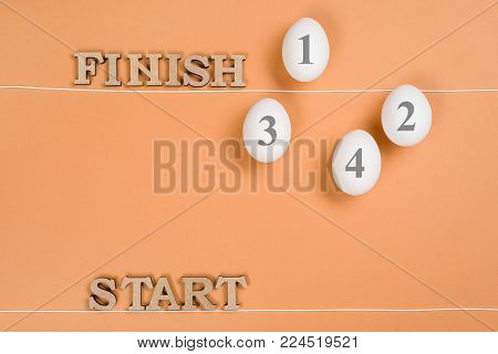Abstract image. The word start and eggs on the way from start to finish. Egg behind the finish line