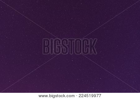 Violet Color Night Starry Sky Background. Night View Of Natural Glowing Stars. View From Eastern Europe At Spring Season.