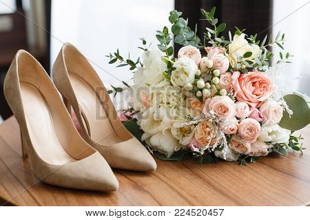 wedding shoes and wedding bouquet of white roses