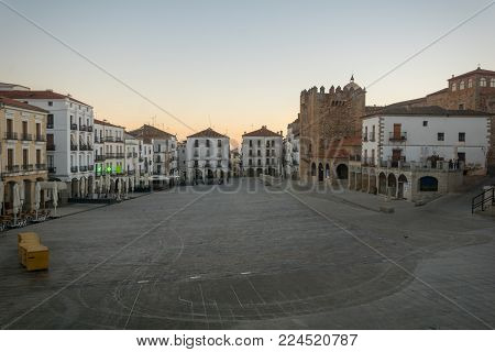 CACERES, SPAIN - DECEMBER 22, 2017: Sunrise scene of the Plaza Mayor (main square), with local businesses, locals and visitors, in Caceres, Extremadura, Spain