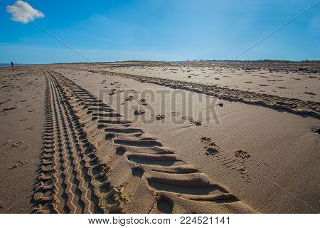 Perspective and vanishing point as tractor tyre tracks lead to the horizon. Tire tracks along a sandy beach.