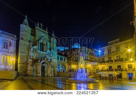 COIMBRA, PORTUGAL - DECEMBER 22, 2017: Evening view of the Santa Cruz monastery, with a Christmas tree, locals and visitors, in Coimbra, Portugal