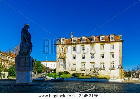 COIMBRA, PORTUGAL - DECEMBER 23, 2017: The statue of D. Dinis (Farmer King), and the Academic museum building, in the old university, in Coimbra, Portugal