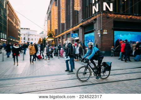 Helsinki, Finland - December 10, 2016: Man Riding Bicycle Near Stockmann Department Store On Aleksanterinkatu Street At Winter Day