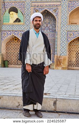 Isfahan, Iran - April 24, 2017: Iranian Mullah in a turban stands in the courtyard of Jame Mosque.