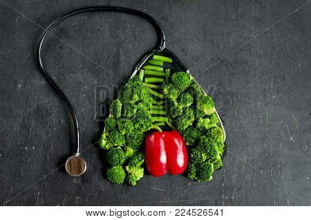 Necessary vegetables for lung and heart health. Broccoli and red pepper lined in the form of lungs and hearts together with a stethoscope on a dark background.