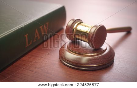3D illustration. Wooden judge hammer with golden details and a law book beside.