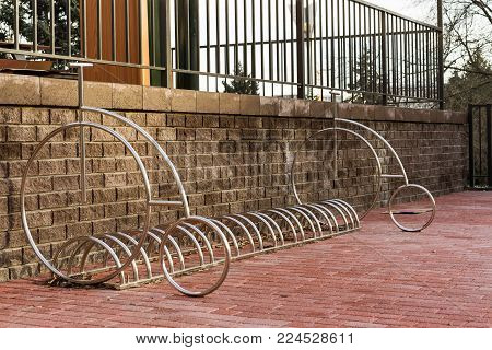 Empty bicycle parking bayi n city park against a brick wall background