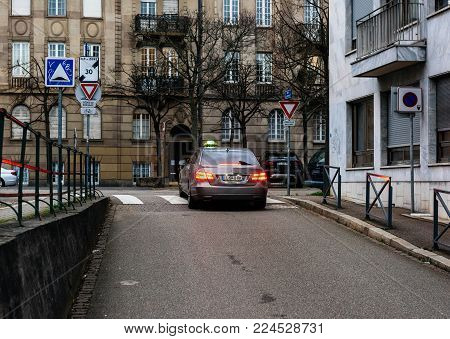 STRASBOURG, FRANCE- JAN 31, 2018: French taxi Mercedes-benz car driving on French street surrounded by beautiful architecture in French style