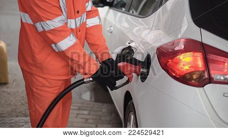 Gas Station Worker Refilling Car At Service Station. Clip. Male Gas Attendant Fills The Car.