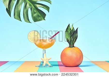 Tropical Grapefruit with Cocktail on Beach.. Bright Summer Color. Hot Summer Vibes. Trendy fashion Style. Creative Art. Fun Summer party Mood. Minimal