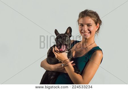 portrait of smile, cute cheerful girl in green, emerald T-shirt, shirt hold young, happy room dog French bulldog, black, active, inquisitive owner at summer. fun friendship. Hairstyle bun of long hair