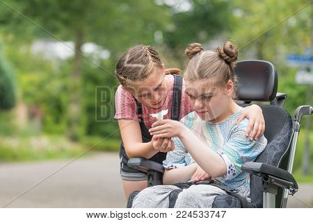 A disabled child outside in a wheelchair with her sister showing her a beautiful white flower. A powerful emotional image showing love and affection of a younger sister to her disabled older sister.