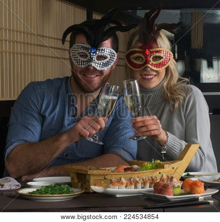 Carnival couple celebrating at sushi restaurant wearing carnival masks.