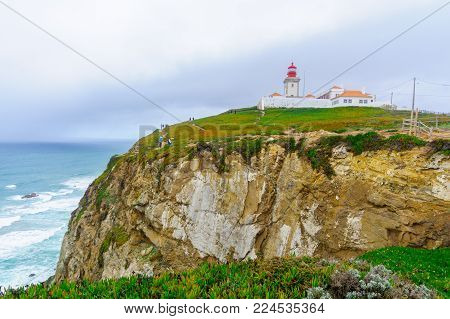 COLARES, PORTUGAL - DECEMBER 28, 2017: View of Cabo (Cape) da Roca, and its lighthouse, with visitors, Portugal. It is the westernmost point in mainland Europe