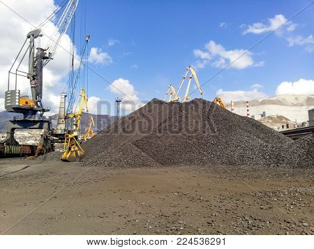 Novorossiysk, Russia - October 10, 2017: Heap of coal anthracite in the port. Port cranes for coal loading.