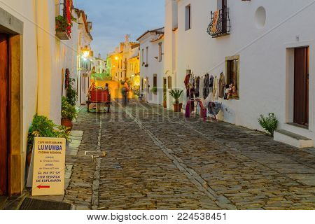 MONSARAZ, PORTUGAL - DECEMBER 29, 2017: Sunset view of Direita street (the main street) in the historic village, with local businesses and visitors, in Monsaraz, Portugal