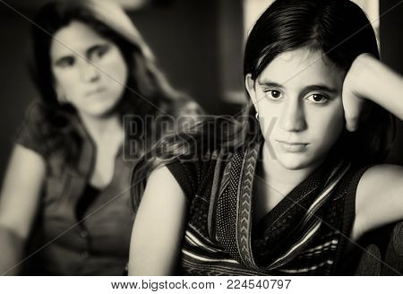 Teenage problems - Defiant teenage girl after a fight with her worried mother looking at her