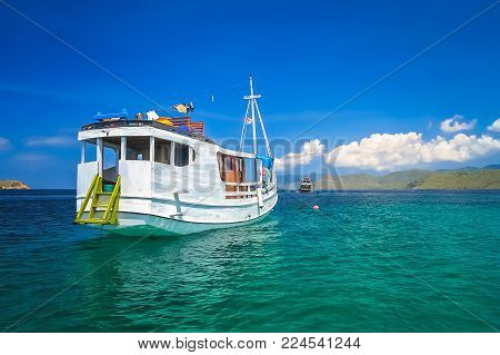Large White Wooden Boat On A Snorkeling Trip Anchored In Clear Ocean Waters On The Shore Of Flores I