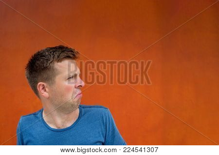 Attractive thoughtful young man is confused and unsure. He is sitting near red wall.