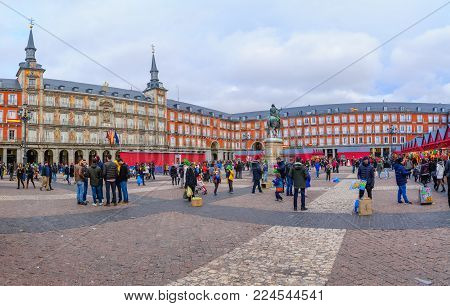 MADRID, SPAIN - DECEMBER 31, 2017: Scene of Plaza Mayor (main square), with a Christmas market, locals and visitors, in Madrid, Spain