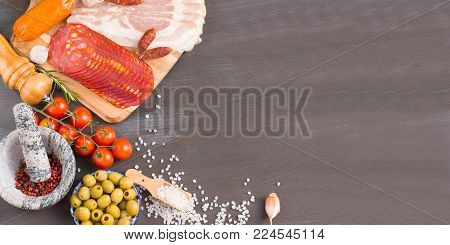 Set of different Spanish appetizer like jamon, prosciutto, bacon, salami and chorizo with spice on a dark wooden background. From top view.