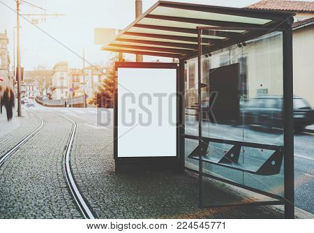 Glass and metal tram stop with railway track near and blank white mock-up of informational banner inside; empty advertising billboard placeholder stand in urban settings next to tramway and city road