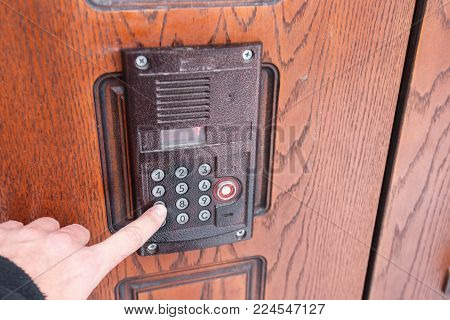 The man's hand dials on the doorphone number 6
