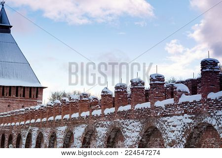 View of the fortress wall. Part of the fortress wall with a tower in Smolensk in the winter. In the foreground the upper part of the fortress wall with a tower on the back blue sky with white clouds.