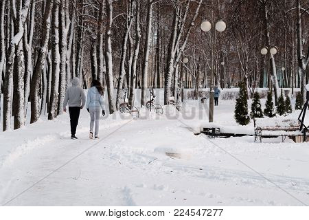 Walk in winter Park. Young couple walking in winter snow-covered Park. In the distance a woman walks with a dog.