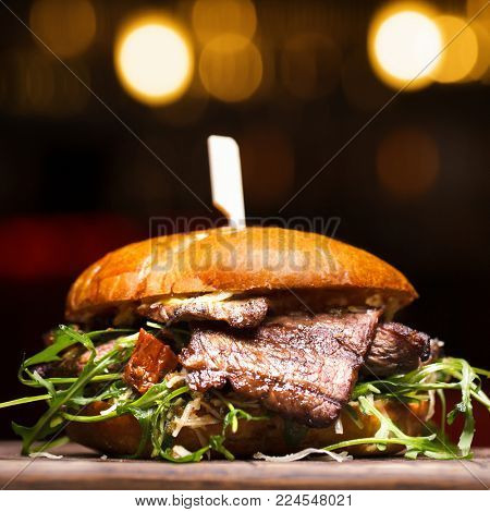 Burger with beef on wooden background. Fresh tasty hamburger with pork, cheese, tomato, onion and lettuce and french fries on a wooden table and dark background with copy space. Close up