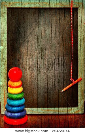empty grunge blackboard in a wooden texture antique frame with a pencil on a string next to a colorful  pyramid.