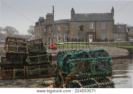 Many lobster pots stacked up on a stone pier in front of old Scottish houses in St. Margaret's Hope, Orkney, Scotland, United Kingdom, on a gray, overcast wet day with a red skiff on green grass in background.