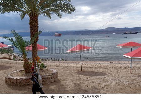 AQABA, JORDAN - MARCH 14, 2014: Service man on the beach of Aqaba in springtime. Aqaba is situated in southernmost Jordan
