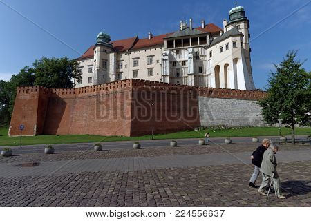 KRAKOW, POLAND - SEPTEMBER 15, 2013: People at the Wawel royal castle. Built in the XVI century, now the castle is the museum and the main attraction of the city