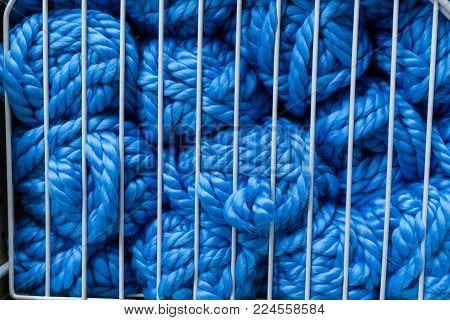 Balls of blue knitting yarn in white metal grid
