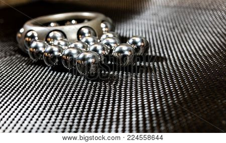 Loose ball bearings in front of an automotive wheel bearing on carbon fiber cloth.