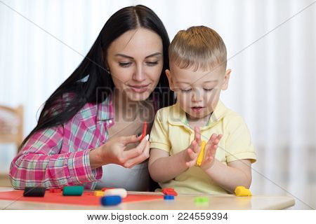 Woman teaches child son handcraft at home