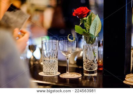 crystal vase with water and a red rose, an empty glass of alcoholic cocktail and a glass half filled with water stand on bar counter