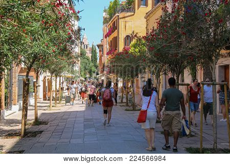 Venice, Italy - August 13, 2016: Tourists walking in street of old city